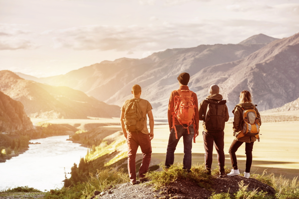Four_friends_stands_on_view_point_and_looking_at_sunset_mountains_and_river_shutterstock_1058312588