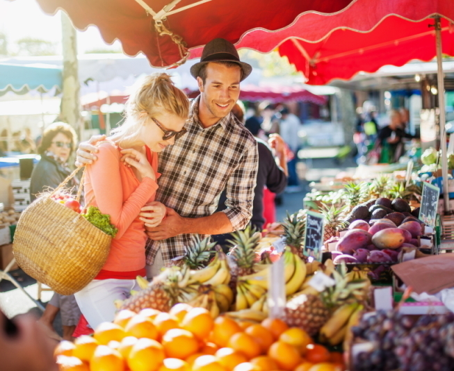 a_young_couple_buying_fruits_and_vegetables_in_a_market_on_a_sunny_morning_the_young_woman_carries_a_basket_shutterstock_233610061d